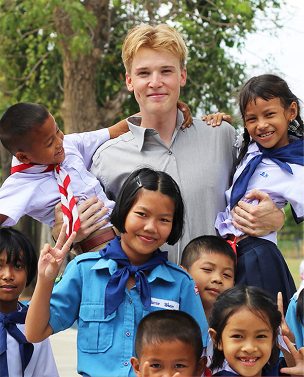 Male teacher in school yard with thai school children